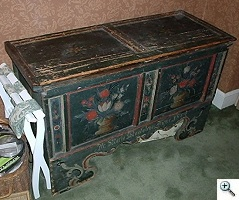 Chest with milk paint decoration produced in Pennsylvania suffering from physical damages and long usage