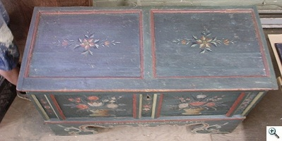 Top of chest shown restored, leaving significant distress intact, not over-restored
